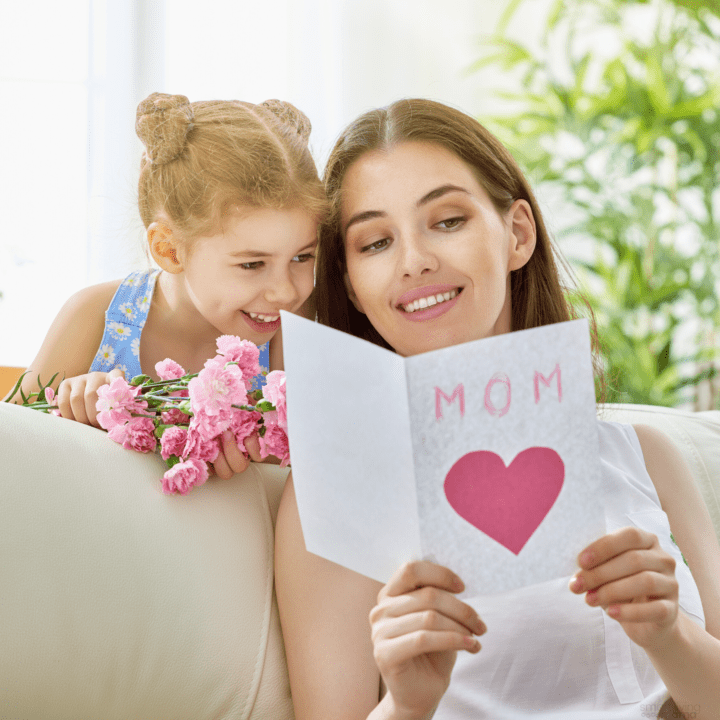 daughter giving mom a mother's day gift and card and both of them are smiling