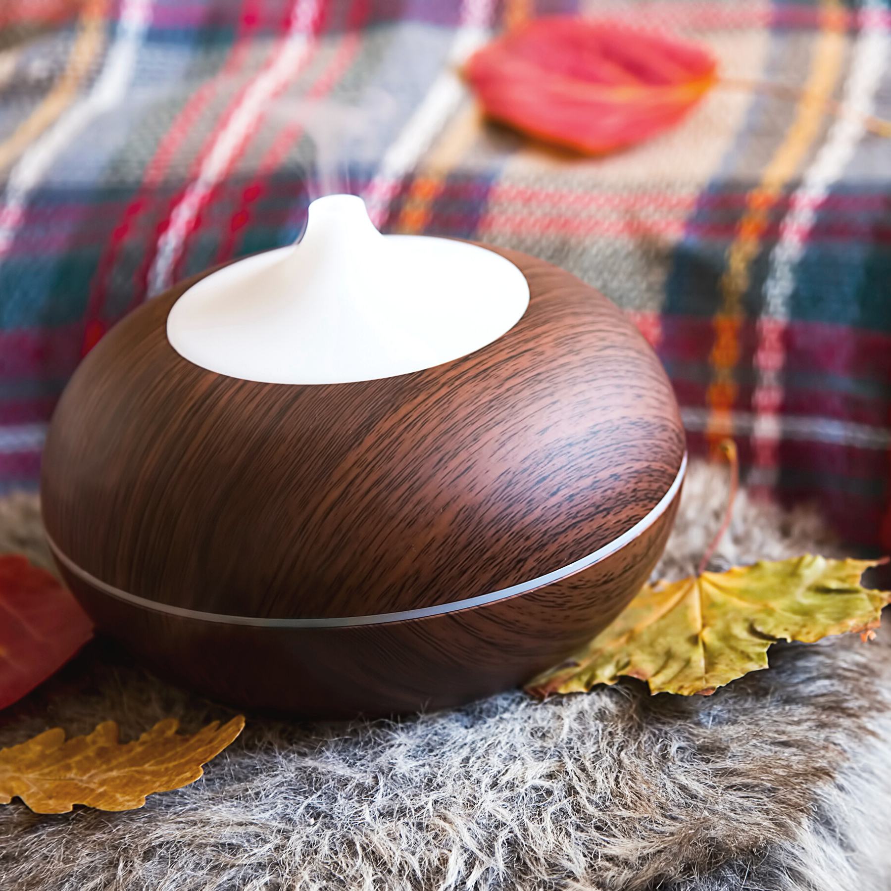 white and dark wood essential oil diffuser sitting on an end table covered with a furry blanket and autumn leaves, with a plaid blanket in the backround