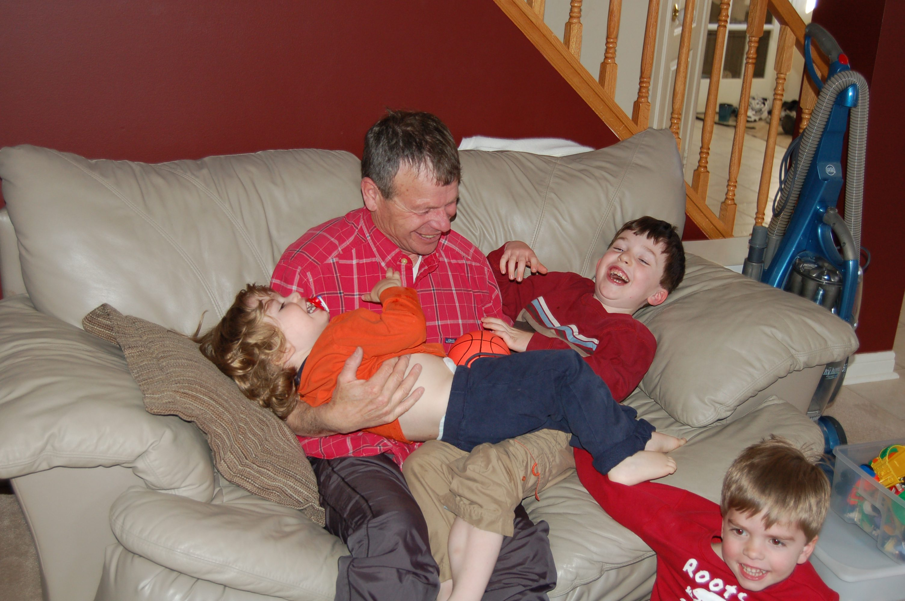 Grandfather wrestling his three grandsons and laughing