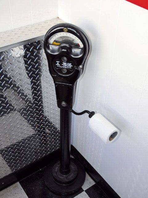 Use a parking meter as a toilet paper holder in a Vintage Car Themed bathroom.