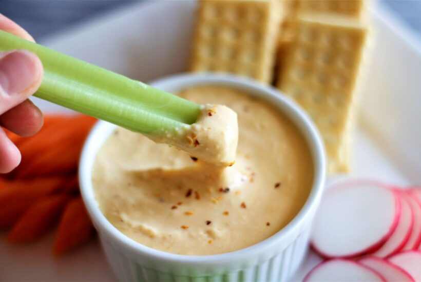 a plate with beer cheese appetizer, crackers, carrots and celery