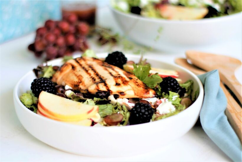 A salad bowl with grilled chicken, blackberries, sliced apples and goat cheese.