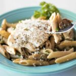 A bowl with penne pasta with a mushroom cream sauce, sliced chicken breast, and grated Parmesan cheese