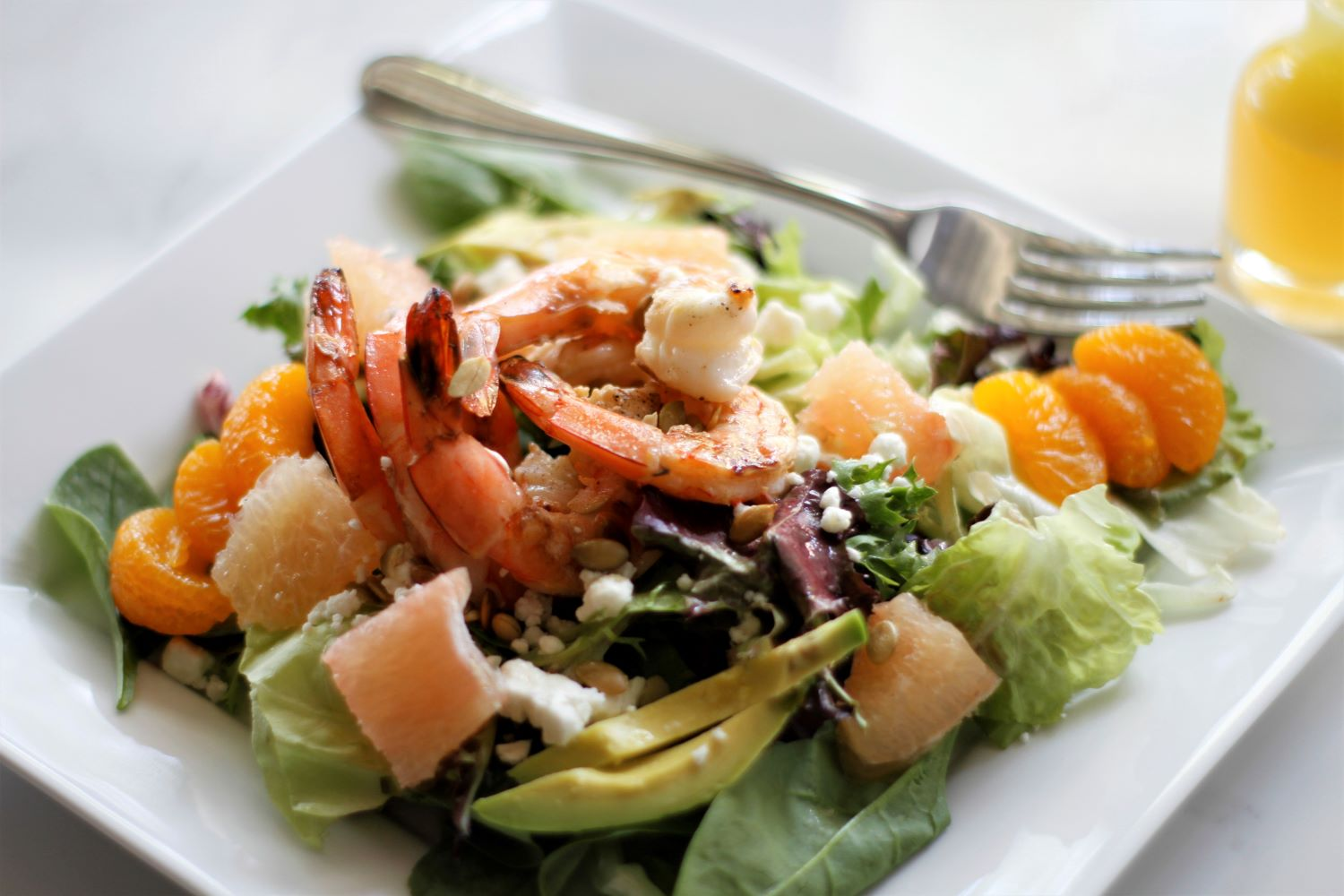 Grilled shrimp in a salad with avocado, grapefruit, madarin oranges and goat cheese