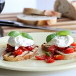 Grilled bread topped with tomatoes and basil with burrata cheese. The appetizer is paired with a glass of red wine.