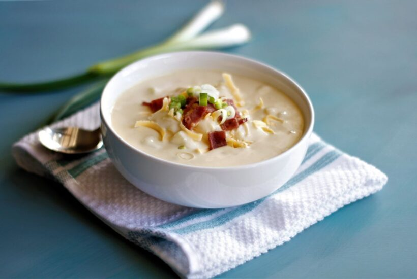 A bowl of potato soup with crumbled bacon, sliced green onions and shreeded cheese on top
