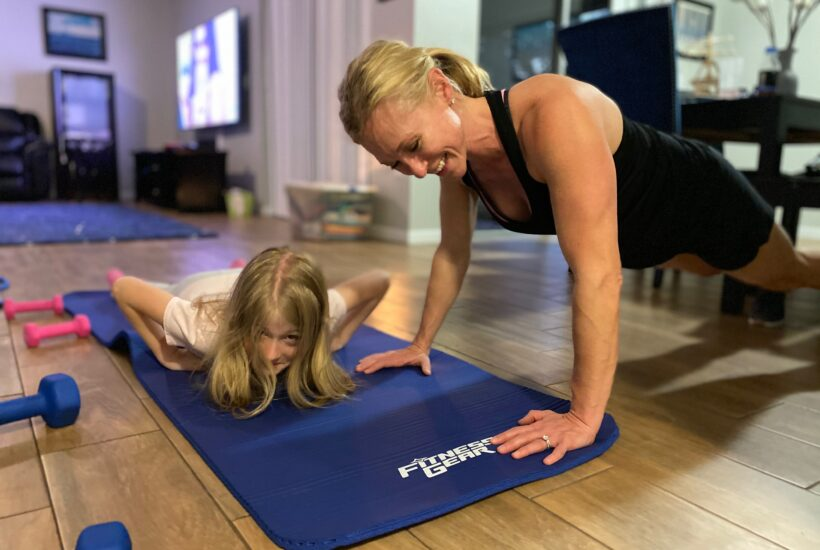 Woman working out in living room with daughter