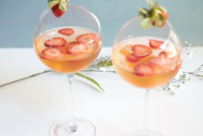 2 wine glasses filled with rosa wine, strawberries and tangerines