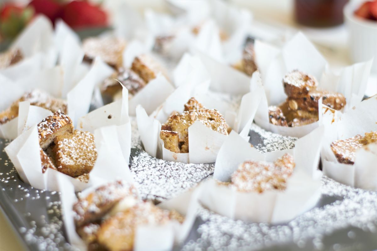 French toast muffins in a muffin tray sprinkled with powdered sugar