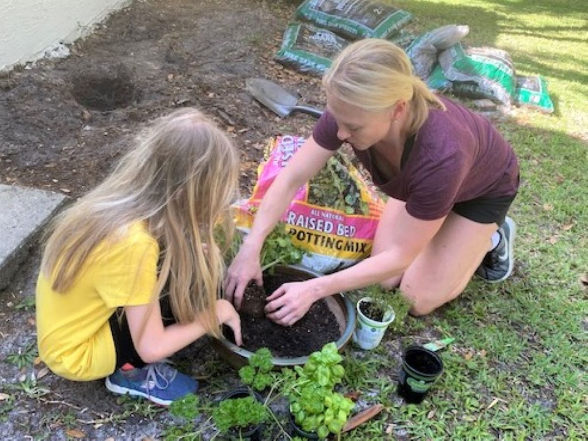 a woman and child planting a herb garden