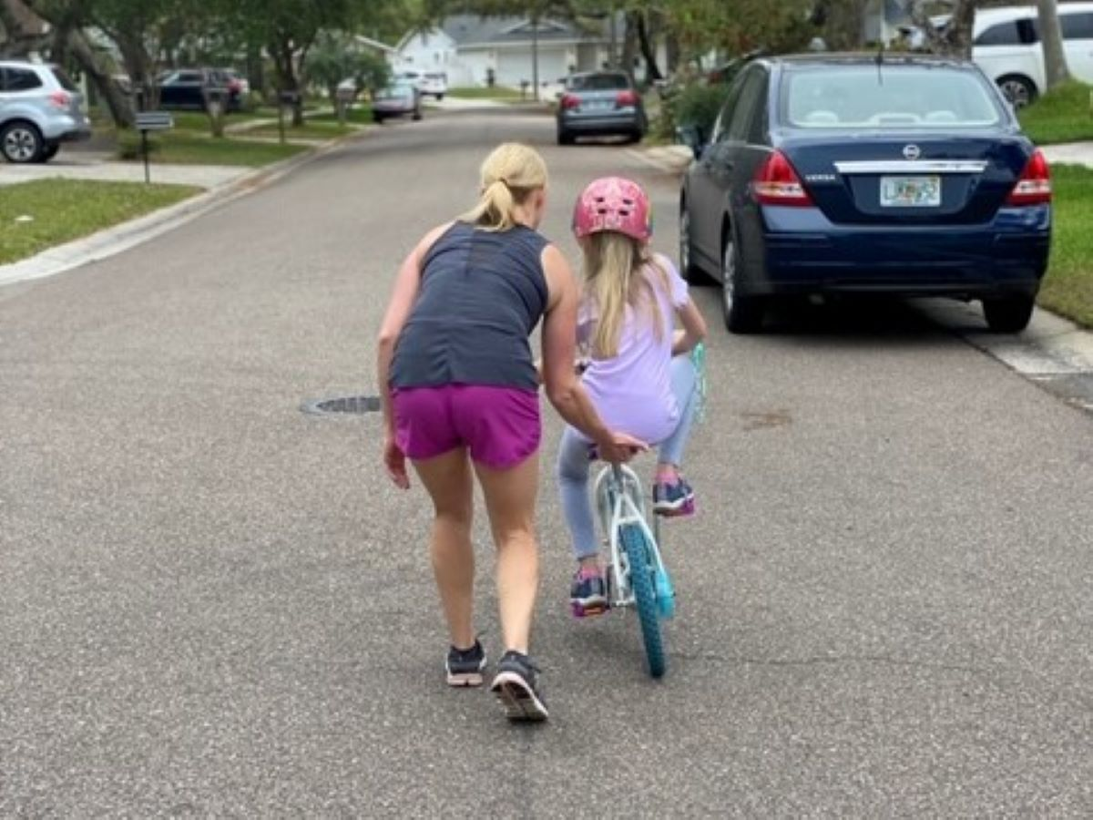 a woman helping a child to learn how to ride a bike