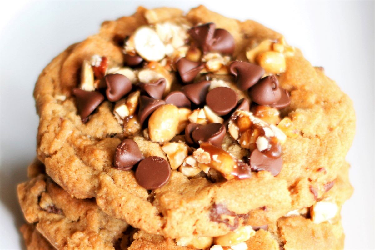 a close up of the top of a peanut butter cookie with chocolate chips and candied peanuts