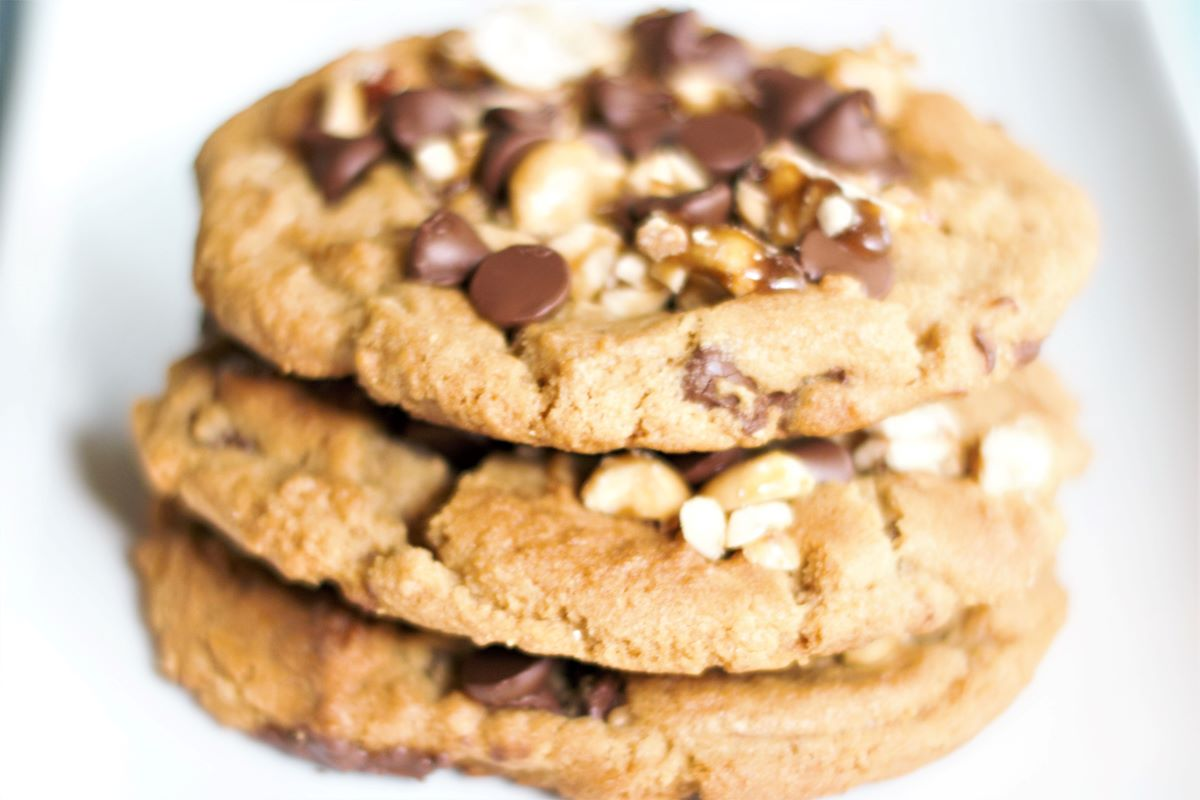 A stack of 3 peanut butter chocolate chip cookies with candied peanuts