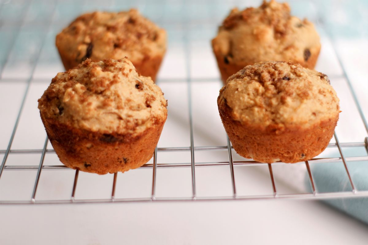four raisin cinnamon muffins cooling on a wire rack