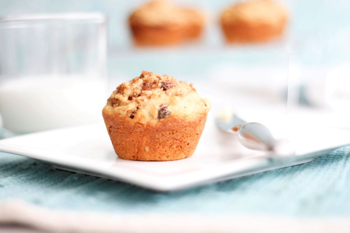 raisin muffin on a plat with knife and butter and a glass of milk