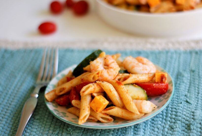 A plate of pasta salad with shrimp, cubed cheese, cucumbers and tomatoes