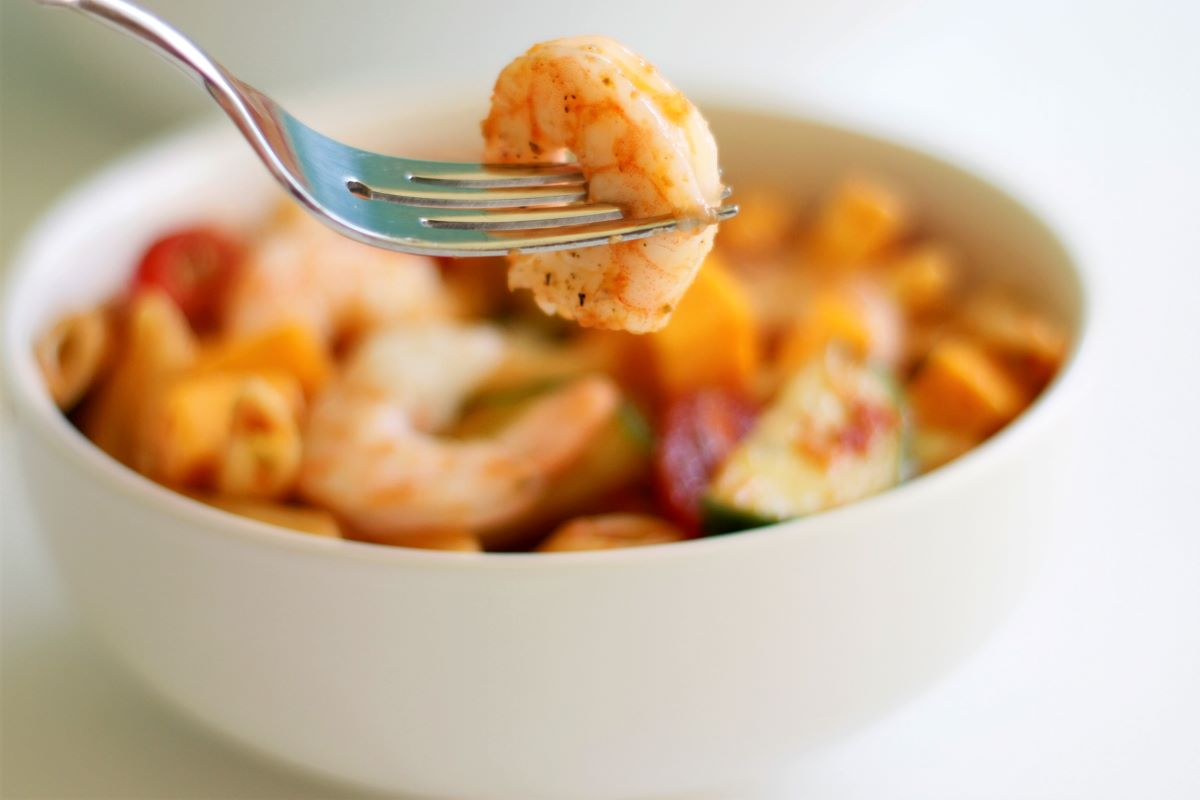 A bowl with shrimp pasta salad and a fork with a shrimp