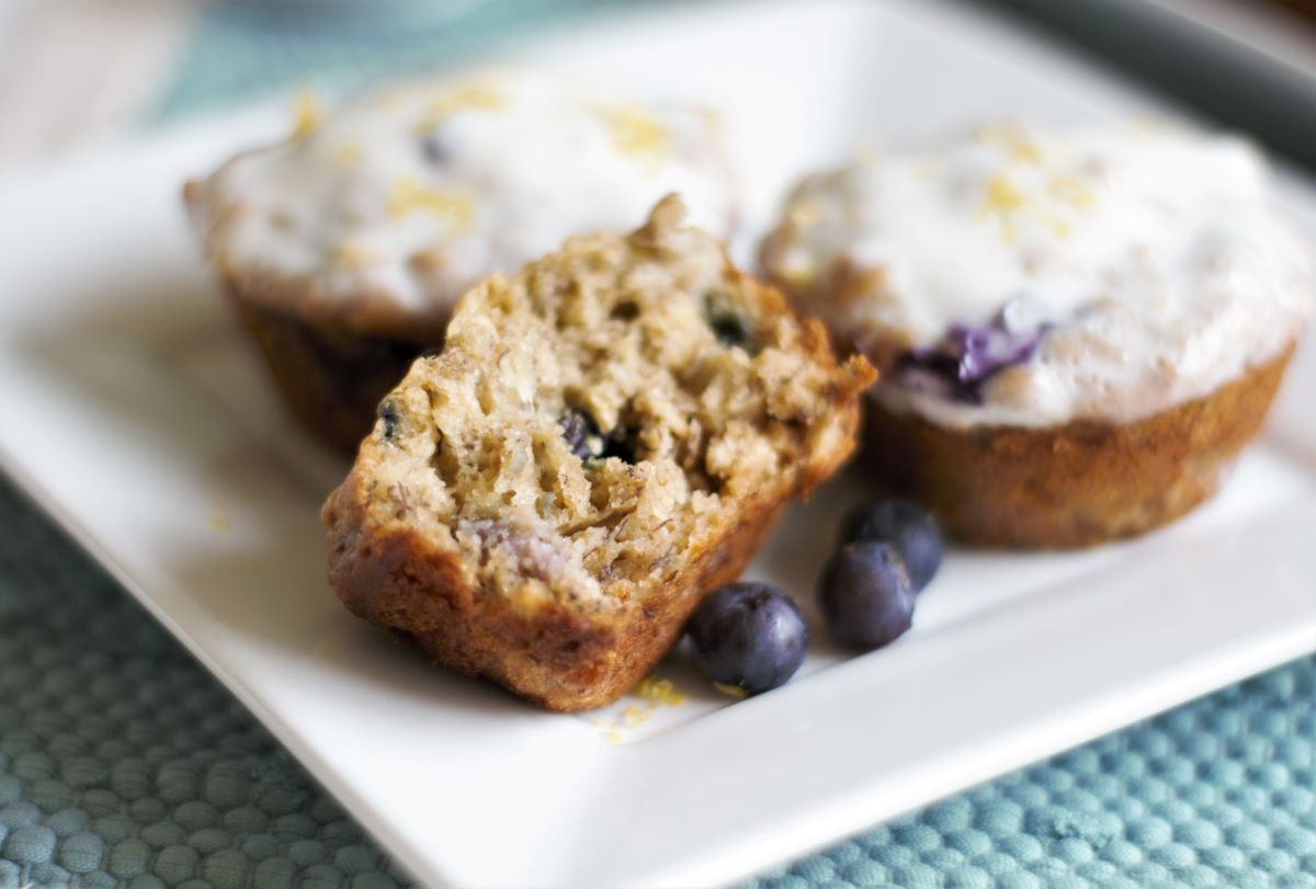 A plate with blueberry banana muffins with lemon glaze
