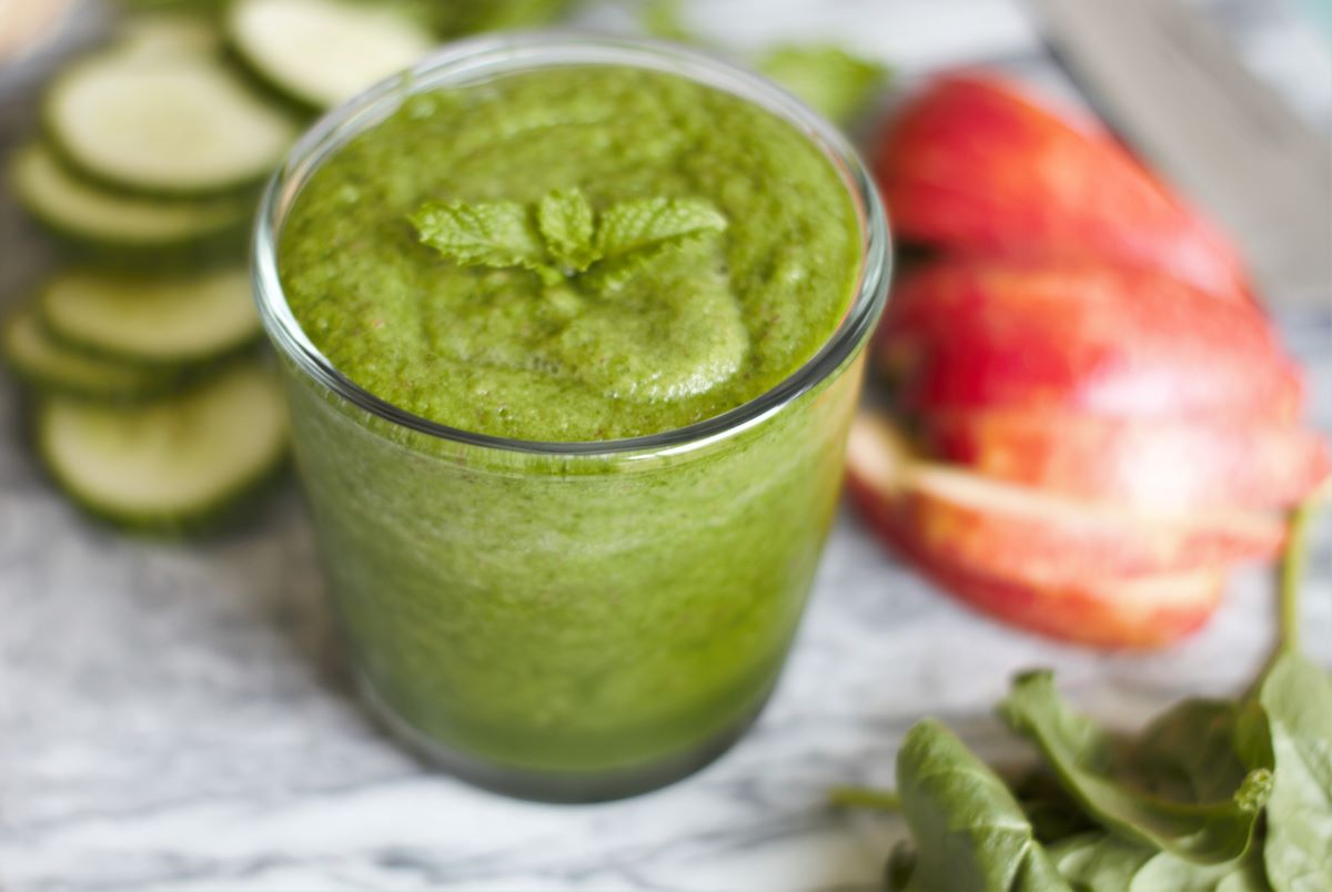 a green smoothie with ingredients of an apple, spinach and cucumber on a cutting board