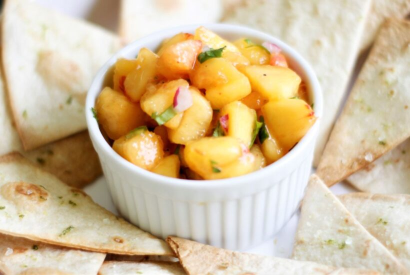a bowl with peach salsa and chips
