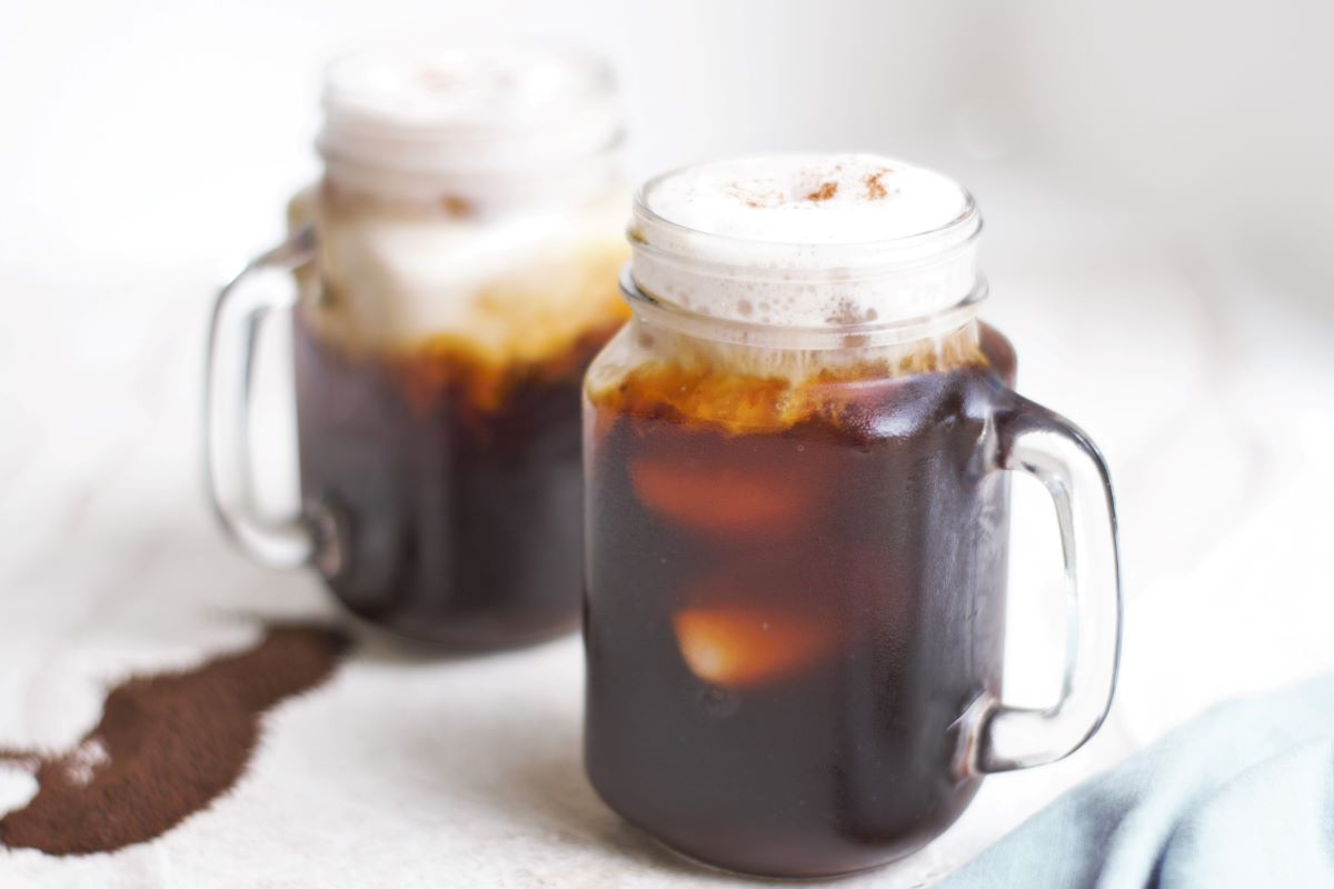 Two mugs of cold brew with cinnamon almond milk foam.