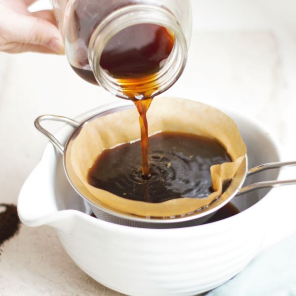 Straining cold brew from a mason jar into a fine mesh sieve