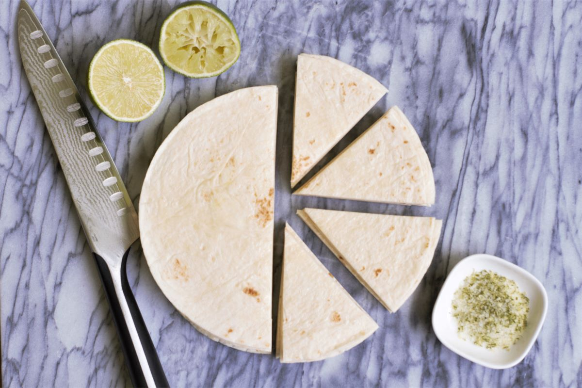 A cutting board showing how to cut tortillas to make homemade chips
