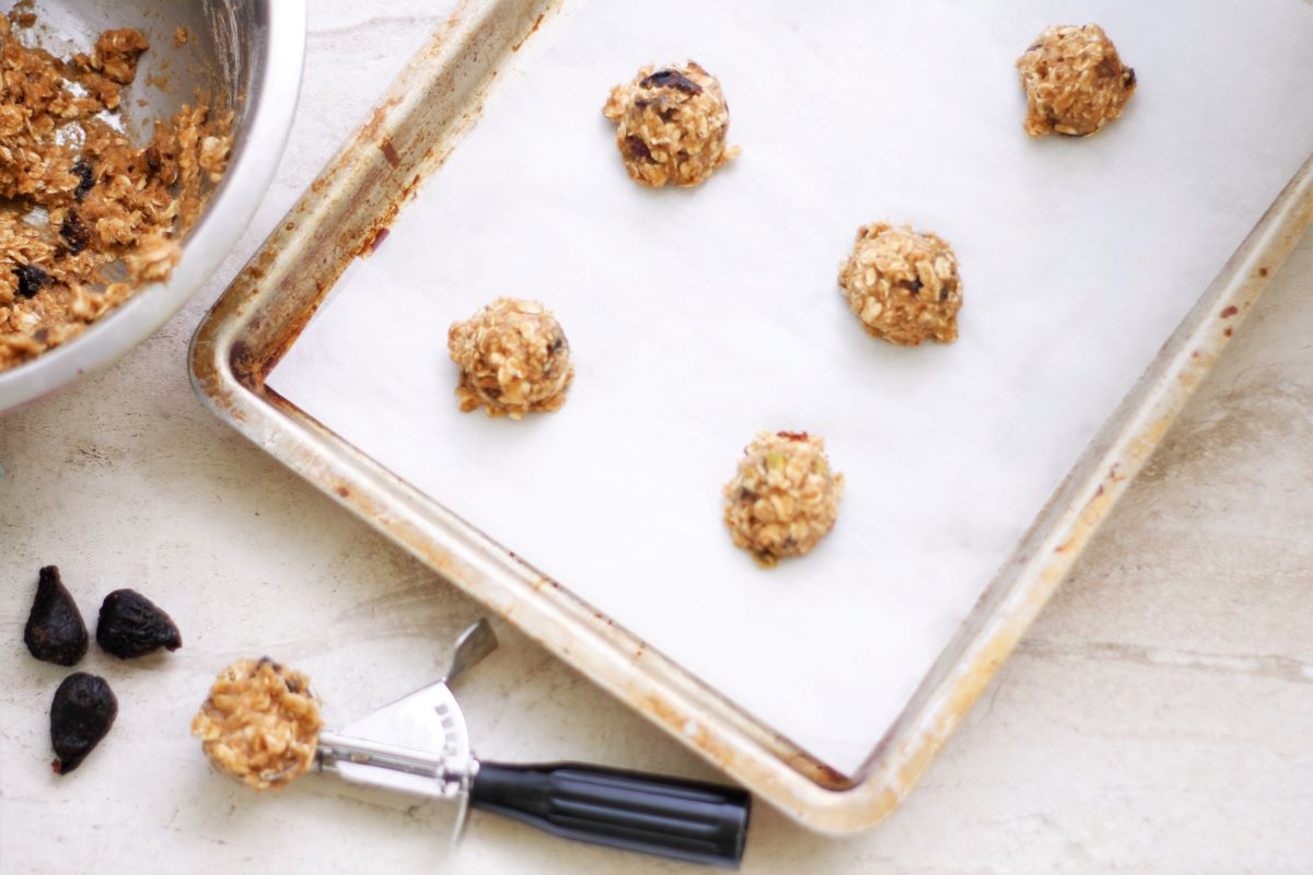 Cookie batter on a cookie sheet with parchment paper and a cookie scoop