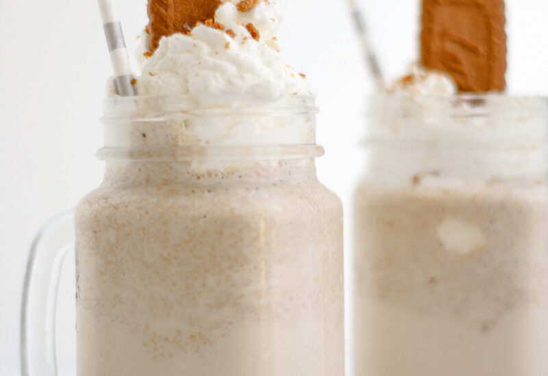 Two milkshakes with topped with whipped cream and a biscoff cookie