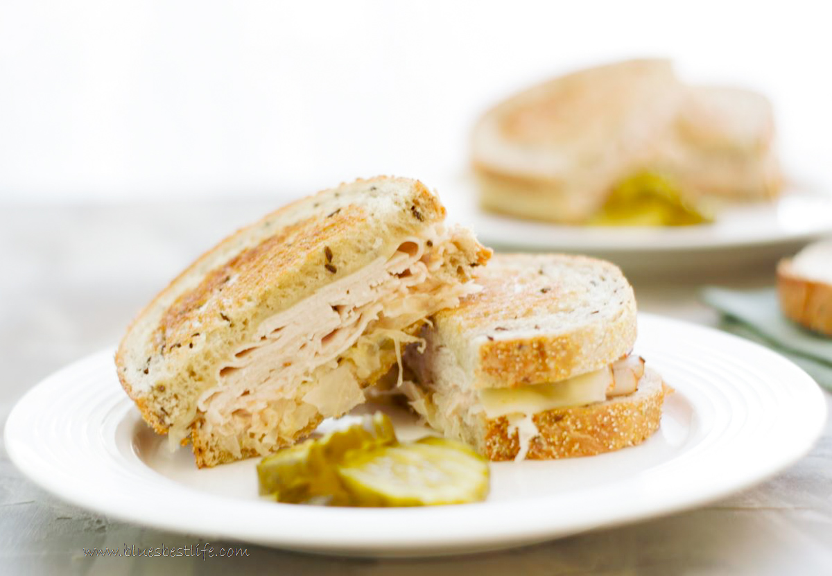 A turkey reuben sandwich on a plate with pickles