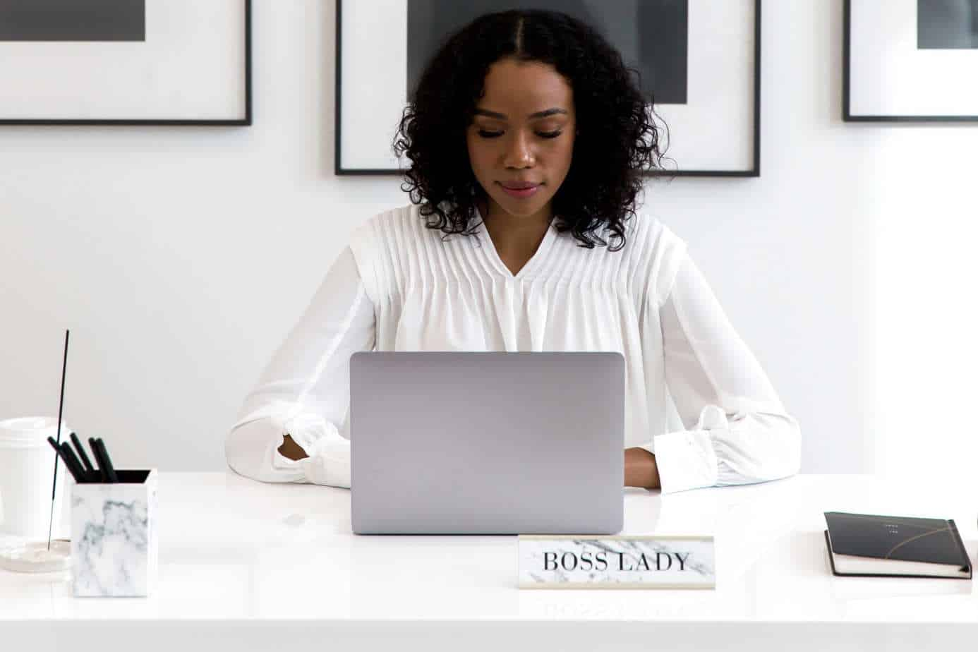 woman at keyboard with notice saying boss lady